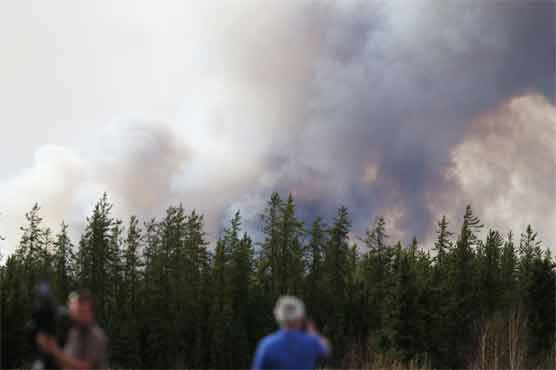 Raging forest fires that prompted evacuation of a Canadian city were advancing more slowly Sunday