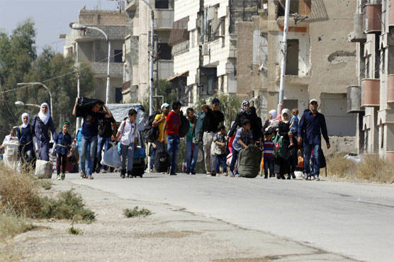 Syrian rebels, families start leaving Damascus neighborhood