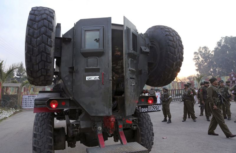 An Indian Army soldier sits in armoured vehicle as others take position at the Sunjwan Army camp in Jammu India.-- AP